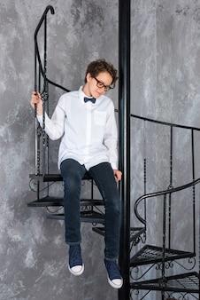Inteligentna nastolatka w okularach siedzi na spiralnych schodach w mieszkaniu na poddaszu nastolatka w białym s...