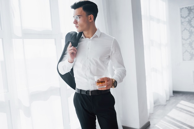 Inteligentna osoba. luksusowo wyglądający mężczyzna w klasycznym stroju stoi w pokoju i trzyma górę garnituru i szklankę z alkoholem.