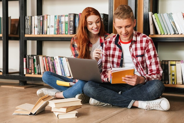 Inteligentna para nastolatków siedzi na podłodze przy półce z książkami