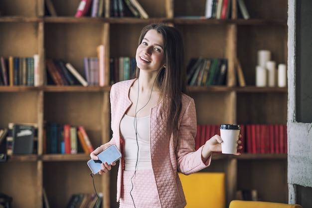 Inteligentna piękna młoda kobieta w słuchawkach ze szklanką kawy w ręku zamiast mikrofonu tańczy i śpiewa do muzyki
