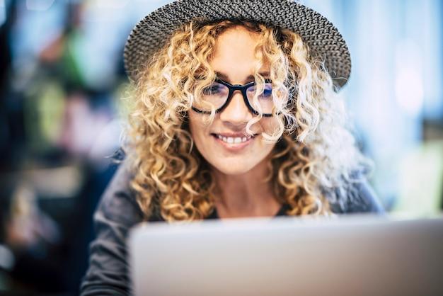 Inteligentna praca w stylu życia w podróży dla pięknej modnej młodej kobiety rasy kaukaskiej używa laptopa w barze lub bramie lotniska nowoczesna alternatywa koncepcja wolnego biura portret ładnych kobiet blondynka