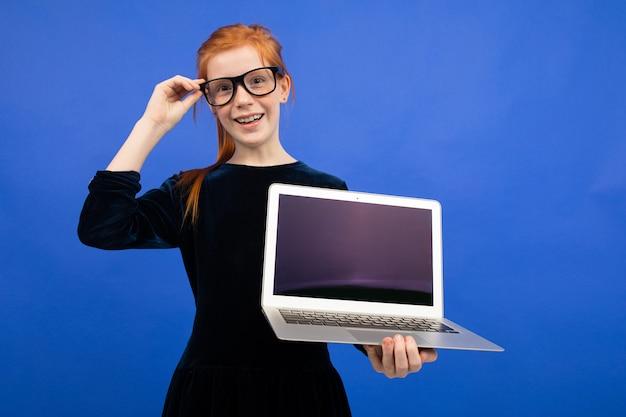 Inteligentna rudowłosa dziewczyna nastolatka w okularach trzyma laptopa z pustym ekranem