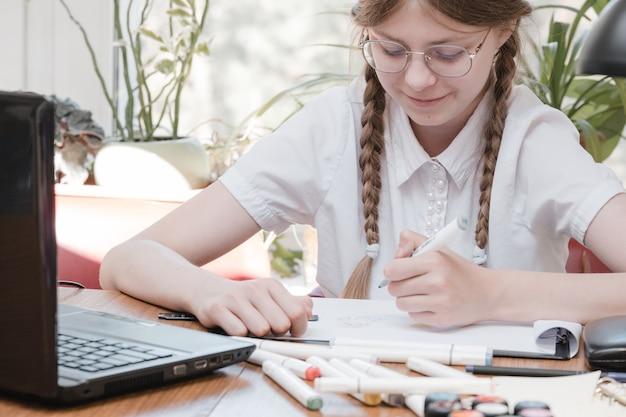Inteligentna uczennica odrabia lekcje siedząc przy biurku, pisze długopisem w swoich notatkach i korzysta z laptopa. uczy się języka online, wykonuje zadania szkolne w domu, słucha wykładów