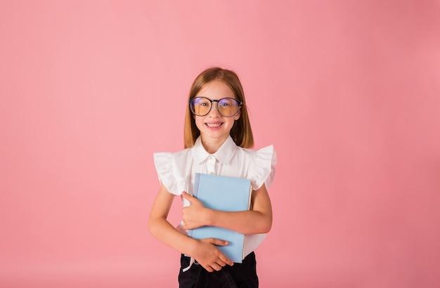 Inteligentna uczennica w mundurku i okularach stoi z niebieskim zeszytem na różowym tle z kopią przestrzeni