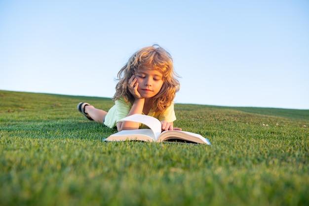 Inteligentne dziecko chłopiec czytanie książki w parku na zewnątrz w letni dzień mądre dzieci