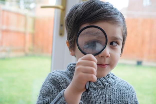 Inteligentne dziecko gospodarstwa i patrząc przez szkło powiększające, pokazując duże oko