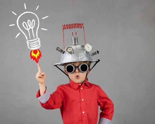 Inteligentne dziecko udaje biznesmena śmieszne dziecko w kasku z żarówką