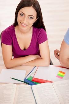 Inteligentne piękno. widok z góry na piękną studentkę siedzącą przy biurku i uśmiechającą się do kamery