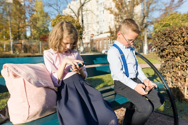 Inteligentne poważne dzieci, chłopiec i dziewczynka, szukają smartfonów