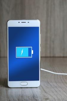 Inteligentne telefony komórkowe ładujące się na drewnianym biurku