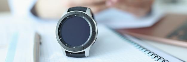 Inteligentne zegarki leżą na notebooku z długopisem w pobliżu człowieka, który trzyma synchronizację smartfona inteligentnego zegarka