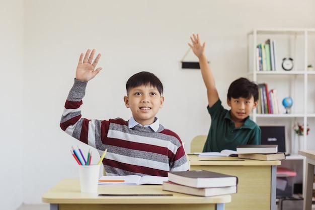 Inteligentni azjatyccy uczniowie szkół podstawowych podnoszą rękę w klasie, aby odpowiedzieć na pytanie nauczyciela