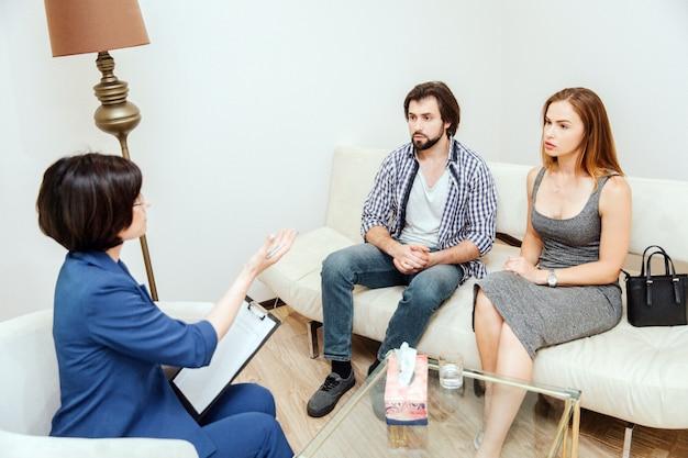 Inteligentni i przystojni ludzie siedzą przed psychologiem i patrzą na nią. lekarz mówi do nich i wyciąga do nich rękę.