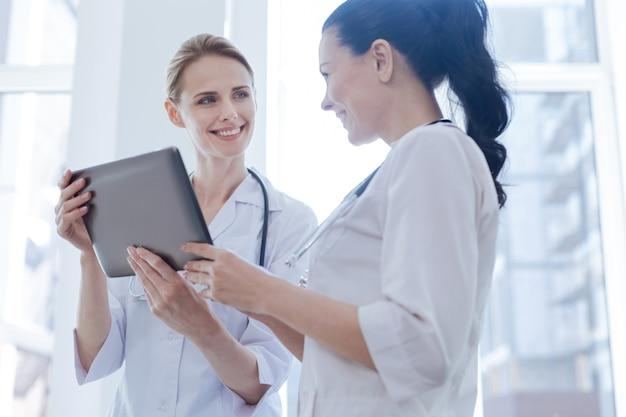 Inteligentni, pozytywni, szczęśliwi onkolodzy pracujący w szpitalu i cieszący się rozmową podczas korzystania z urządzenia cyfrowego