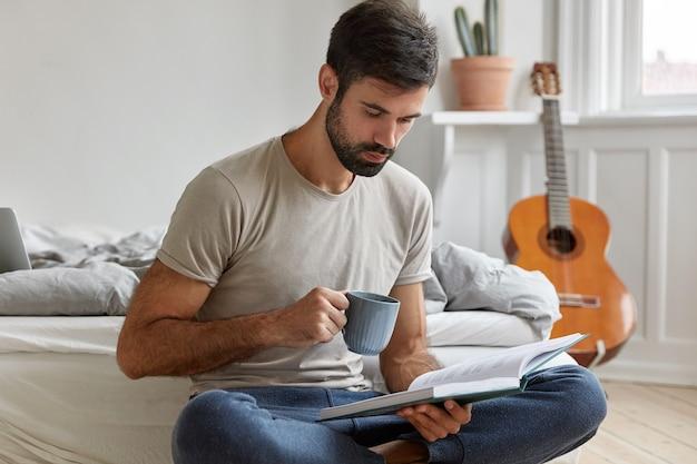 Inteligentny brodaty facet pozuje w domu podczas pracy