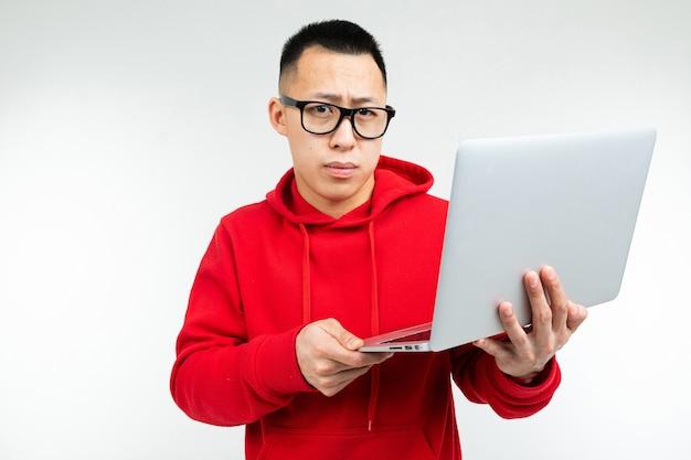 Inteligentny brunetka mężczyzna w okularach w czerwonej bluzie z kapturem, wpisując laptopy