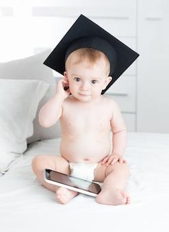 Inteligentny chłopczyk w czapce ukończenia szkoły za pomocą cyfrowego tabletu