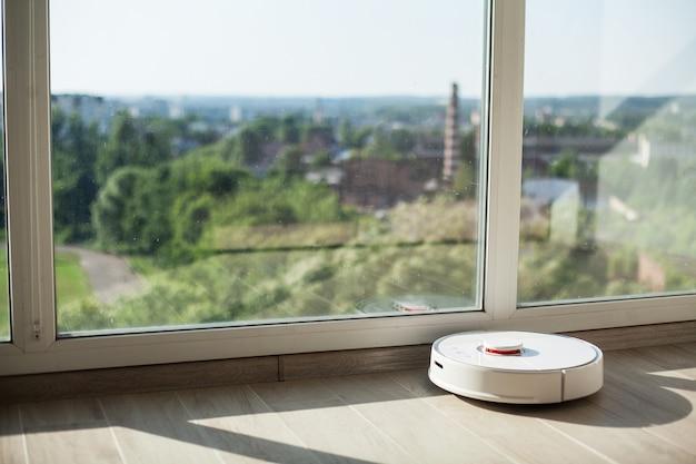 Inteligentny dom, robot odkurzacza działa na drewnianej podłodze w salonie
