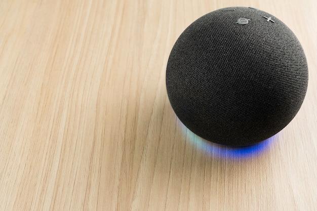 Inteligentny głośnik i wirtualny asystent. służy do utrzymywania łączności w domu i wydawania poleceń głosowo innym urządzeniom elektronicznym. nowoczesna technologia. drewniane tło.