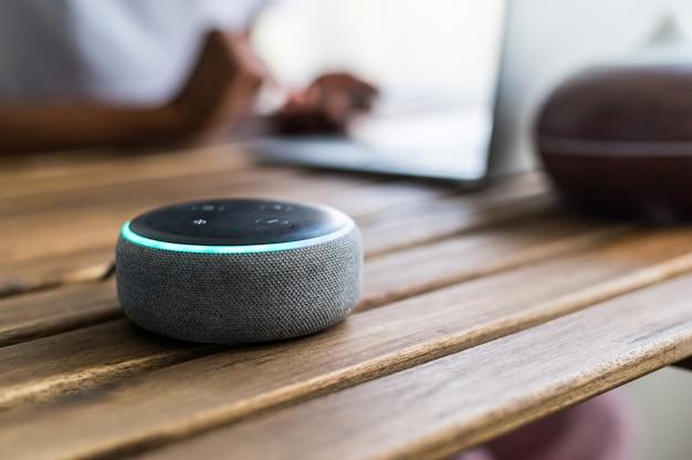 Inteligentny głośnik umieszczony na stole w pobliżu upraw czarnej kobiety za pomocą laptopa w domu