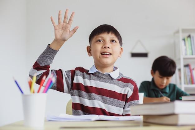 Inteligentny i aktywny uczeń z azji podnosi rękę podczas lekcji, aby odpowiedzieć na pytanie