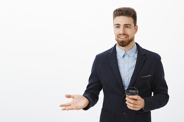 Inteligentny i kreatywny charyzmatyczny przedsiębiorca męski w stylowym garniturze trzymający papierowy kubek z kawą podczas przerwy rozmawiający z partnerem biznesowym, omawiający pracę i pieniądze, gestykulujący z uśmiechem na dłoni pewny