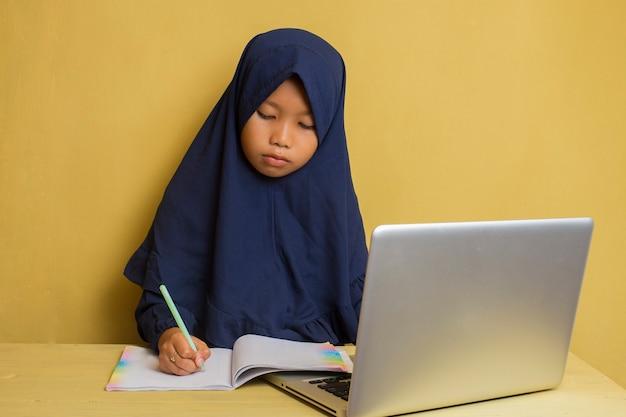 Inteligentny mały azjatycki muzułmański hidżab dziewczyna używa swojego laptopa