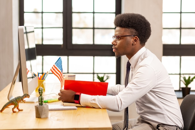 Inteligentny młody biznesmen siedzący w biurze, skupiający się na swojej pracy