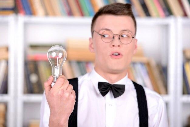 Inteligentny młody człowiek trzyma żarówkę stojąc w bibliotece