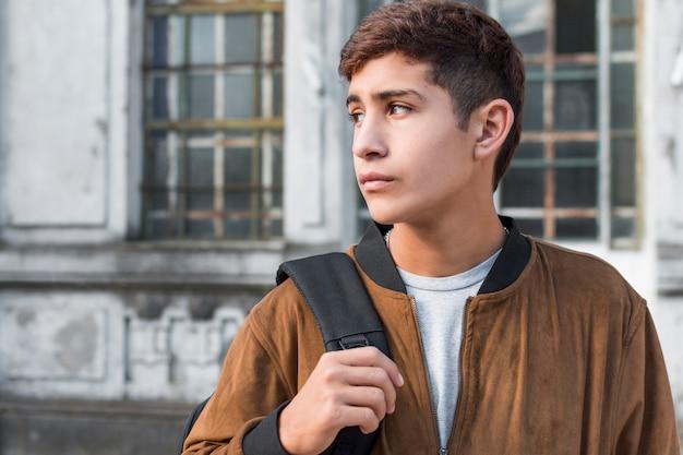 Inteligentny nastoletni chłopak niosąc plecak patrząc od hotelu