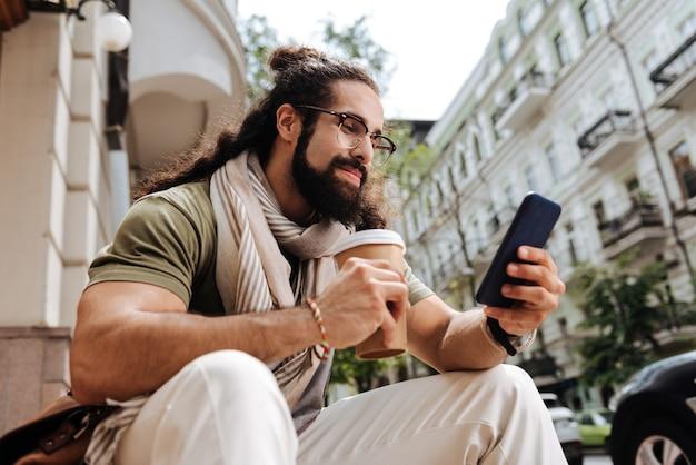 Inteligentny pozytywny człowiek uśmiecha się podczas korzystania ze swojego smartfona