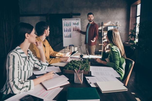 Inteligentny profesjonalny dyrektor generalny przedstawia strategię rozwoju przedsiębiorstwa rozpoczynającego działalność punkt biała tablica wykresy papierowe osoby siedzą przy stole
