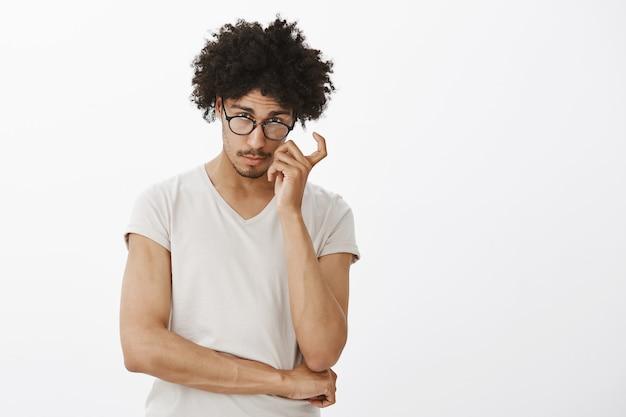 Inteligentny przystojny mężczyzna programista wyglądający zaciekawiony, w okularach