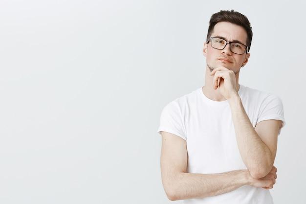 Inteligentny, rozważny facet w okularach, myślący, wyglądający na zaintrygowanego