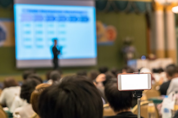 Inteligentny telefon komórkowy robi transmisję na żywo do asian speaker z przypadkowym garniturem na scenie pre