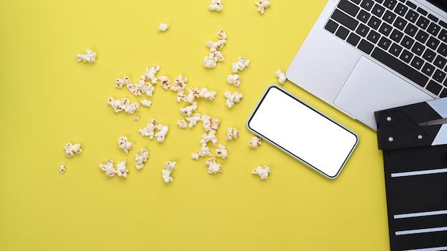 Inteligentny telefon, laptop, clapboard i popcorn na żółtym tle.