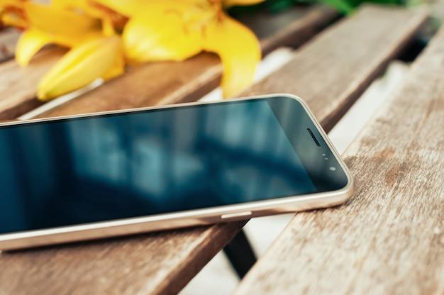 Inteligentny telefon na stole, niewyraźne żółte kwiaty