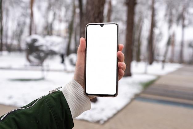 Inteligentny telefon w ręce kobiety w winter park. biały ekran.