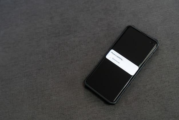 Inteligentny telefon wyświetla aktualizację na ekranie z kopiowanym tekstem. aktualizacja koncepcji informacji o systemie.