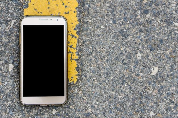 Inteligentny telefon z czarnym ekranem na drodze