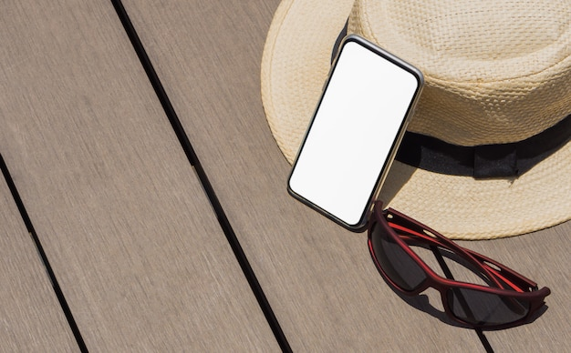 Inteligentny telefon z pustym białym ekranem i słomkowym kapeluszem z czarną wstążką i okularami przeciwsłonecznymi na drewnianej podłodze