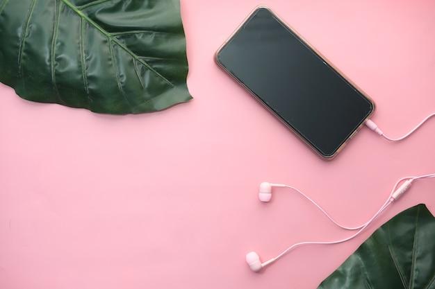 Inteligentny telefon z pustym ekranem, słuchawki na różowym tle.