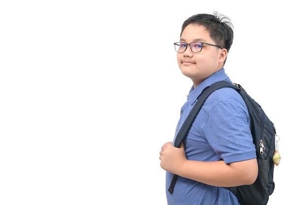 Inteligentny uczeń chłopiec nosi okulary i niebieską koszulkę polo z tornisterem na białym tle, powrót do koncepcji szkoły i edukacji