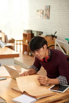 Inteligentny uczeń czytający książkę przy swoim stole, aby znaleźć informacje