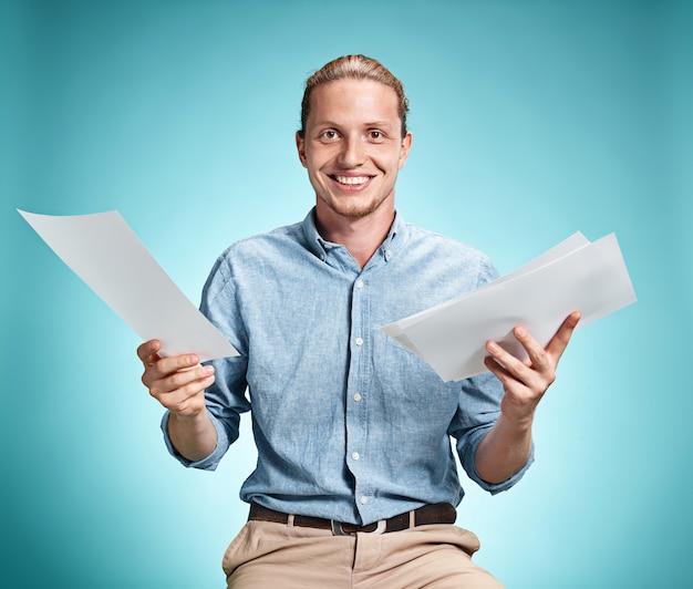 Inteligentny, uśmiechnięty uczeń z doskonałym pomysłem trzymający kartki papieru