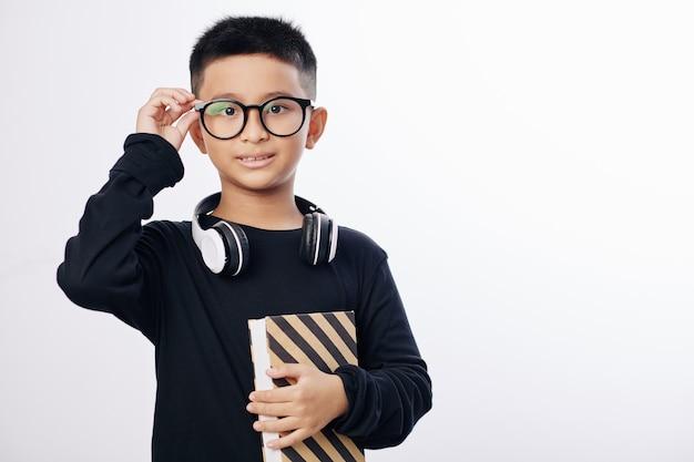 Inteligentny wietnamski preteen boy z książką, dostosowując okulary i patrząc na kamery