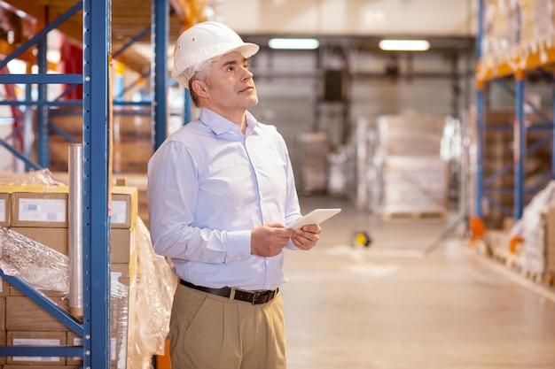 Inteligentny, wykwalifikowany człowiek kontrolujący pracę w magazynie będąc kierownikiem logistyki