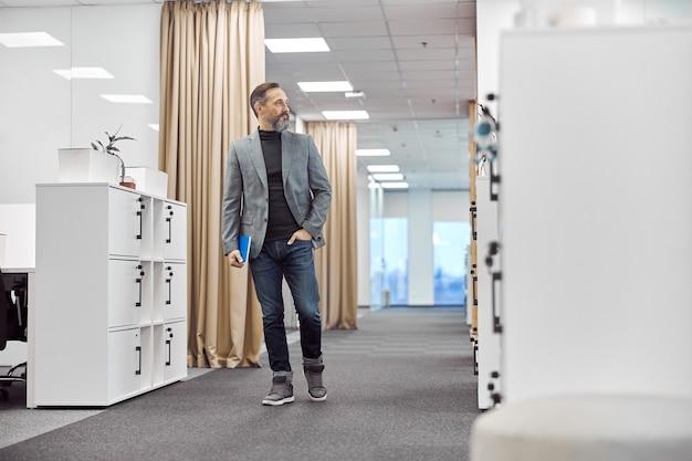Inteligentny zadowolony pracownik biurowy idzie w nowoczesnym biurze