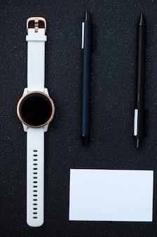 Inteligentny zegarek i inteligentny długopis na czarnym tle
