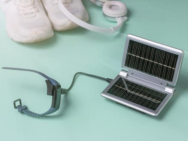 Inteligentny zegarek ładuje się z przenośnej ładowarki na tle trampek i słuchawek. wykorzystanie energii słonecznej. technologia przyszłości.